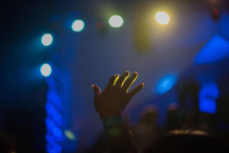 Cropped hand of woman in illuminated music concert