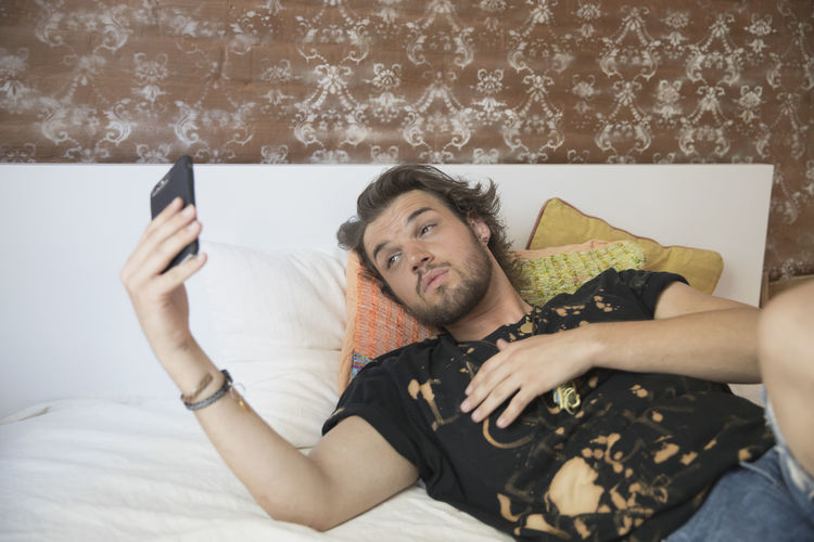 Midsection of man using mobile phone on bed at home