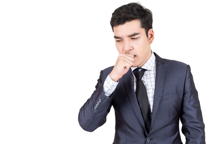 Young businessman coughing against white background