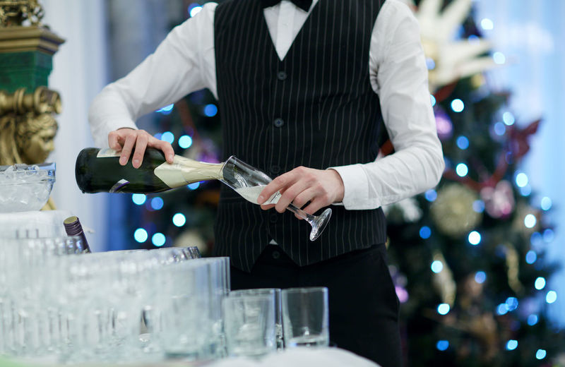 Midsection Of Waiter Pouring Champagne In Restaurant