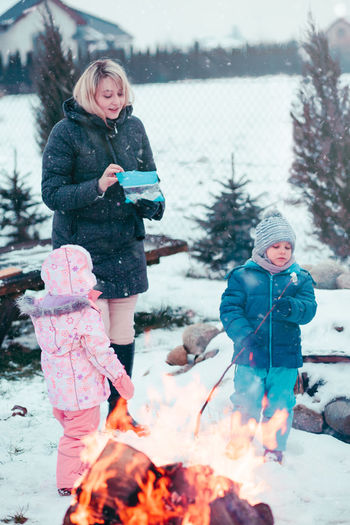 Family spending time together outdoors in the winter. Parents with children gathered around the campfire preparing marshmallows and snacks to toasting over the fire using wooden sticks Winter Child Outdoors Childhood Boy Girl Cold Enjoyment Enjoy Kid Children Wintery Winter Snow Snowing Picnic Family Eating Campfire Roasting Marshmallows Snack Roasted Spending Time