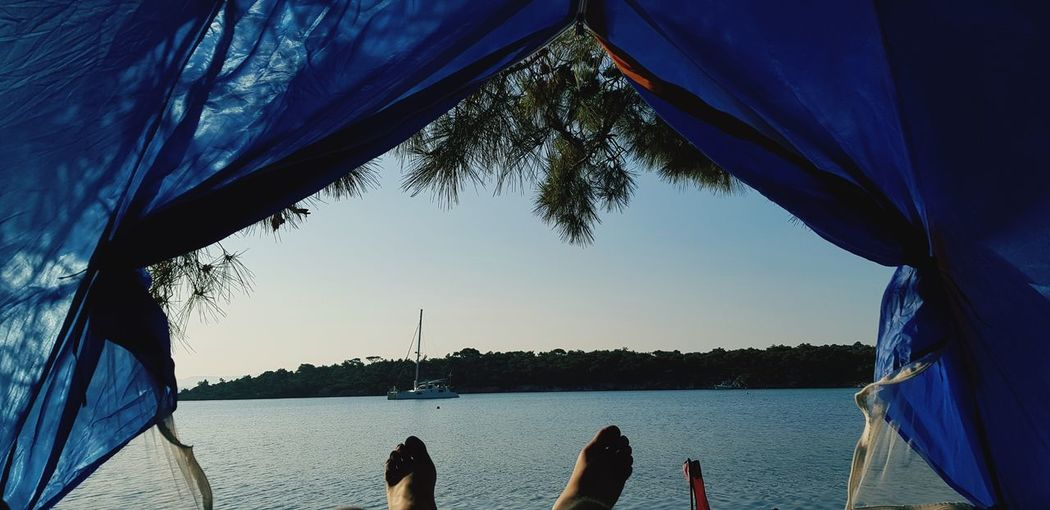 Low section of person in tent against sea and sky