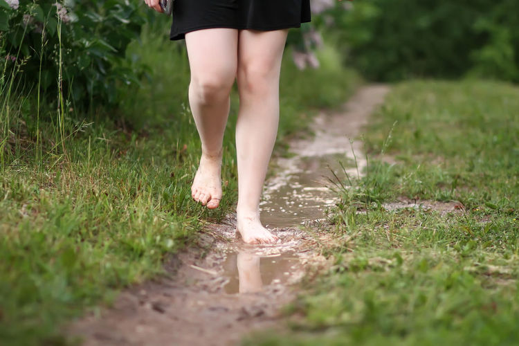 Low section of woman walking walking in puddle