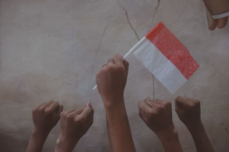 Cropped hands of people holding flag against wall