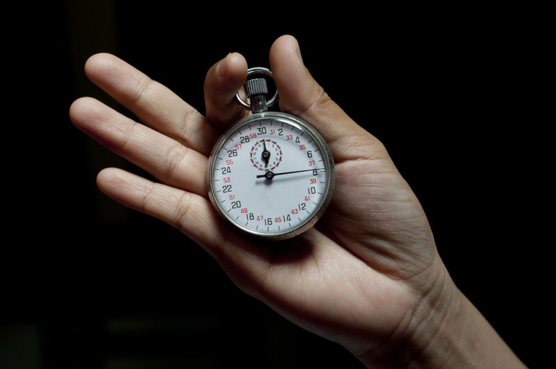 Cropped hand holding stopwatch against black background