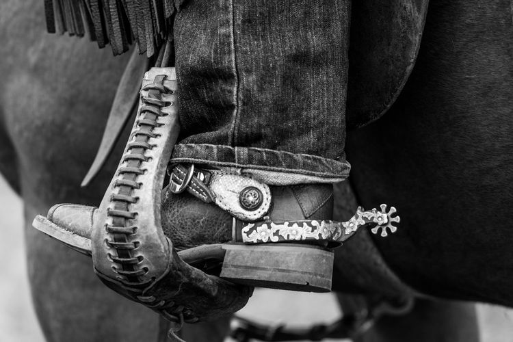 Low section of cowboy riding horse