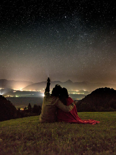 Rear view of couple with flashlight against constellation