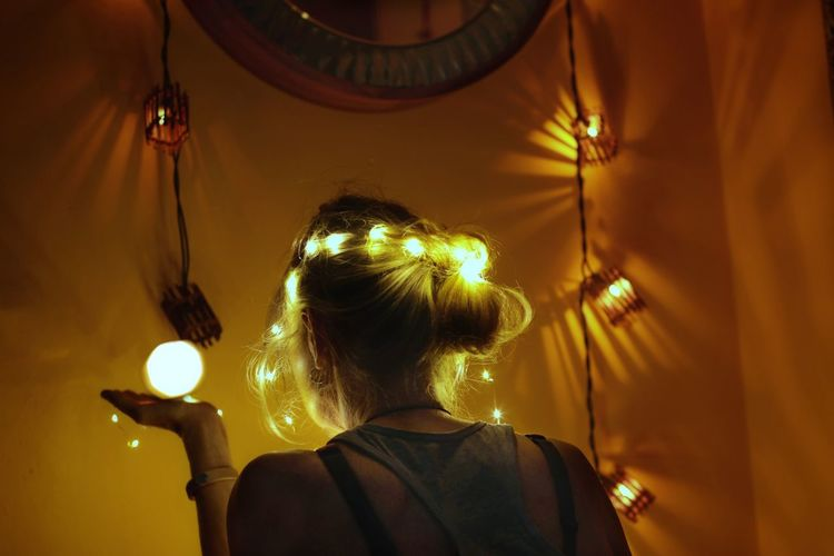 Rear view portrait of woman standing against illuminated lights
