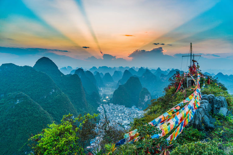 Scenic view of sunset over karst mountains and prayer flag