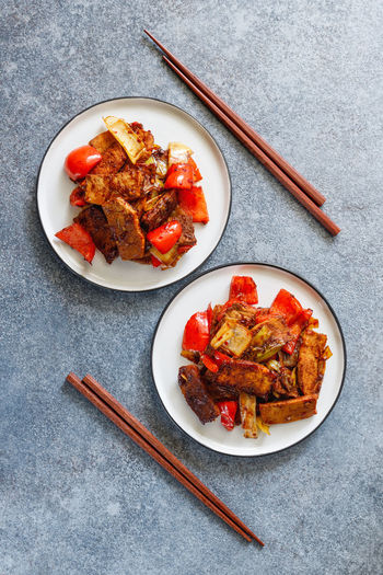 Szechuan Dish ASIA Asian  Food Pork Fried Cooked Two Dinner Persons Sticks Vegetables Spicy Chili. Hot Recipe Portion Top Above View Plate Bowl Pieces Soy Sauce Fry Wok Chinese Roasted Pan Meat Pepper Bell Leek Onion Ready-to-eat Food And Drink Freshness Directly Above Chopsticks Chicken Chicken Meat Indoors  Table No People Wellbeing High Angle View Still Life Kitchen Utensil Healthy Eating Eating Utensil White Meat Temptation