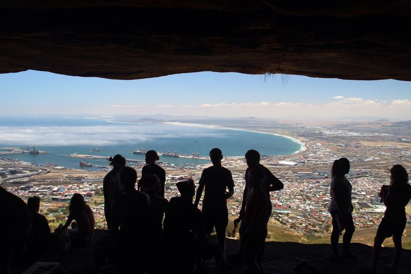 People at table mountain looking view of sea and cityscape