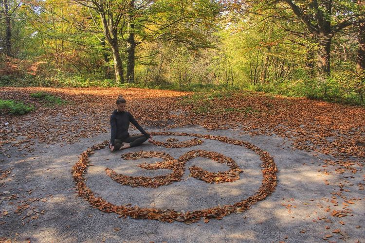 Woman meditating while sitting by symbol on land
