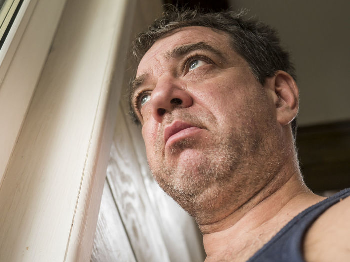 Low angle view of man looking away at home