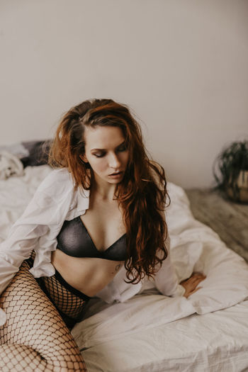 Seductive young woman lying on bed at home
