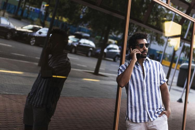 Full length of man using mobile phone on street in city