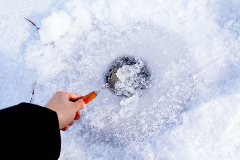 Cropped hand of woman cracking frozen ice outdoors