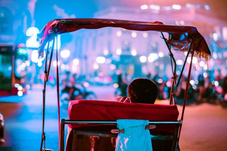 Man talking on mobile phone while sitting in cart at night