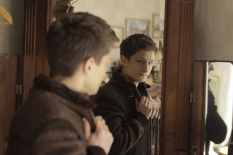 Young man looking in mirror at home