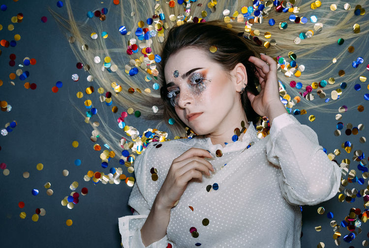 Portrait of woman with confetti against wall