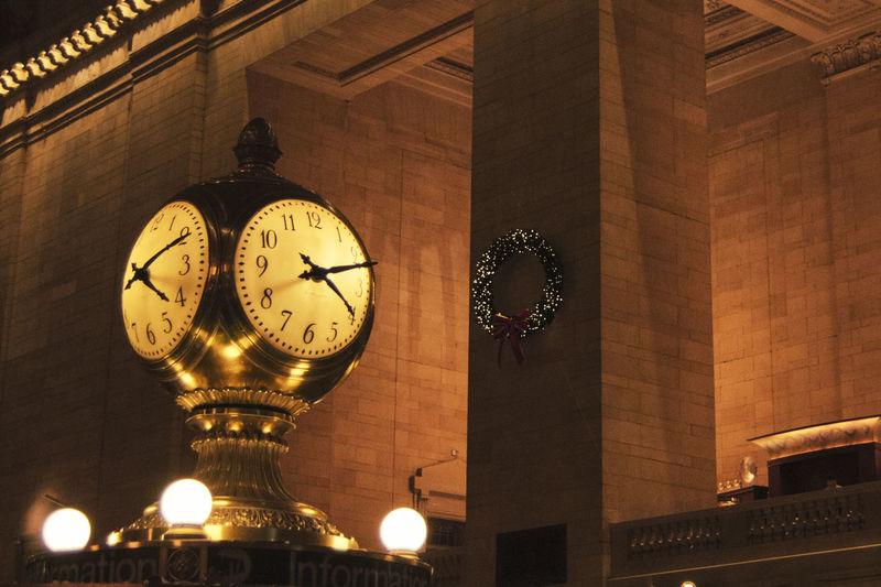 Low angle view of illuminated clock at night