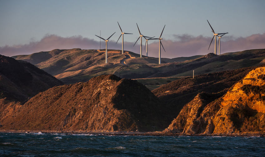 Sea against windmills on mountains during sunset