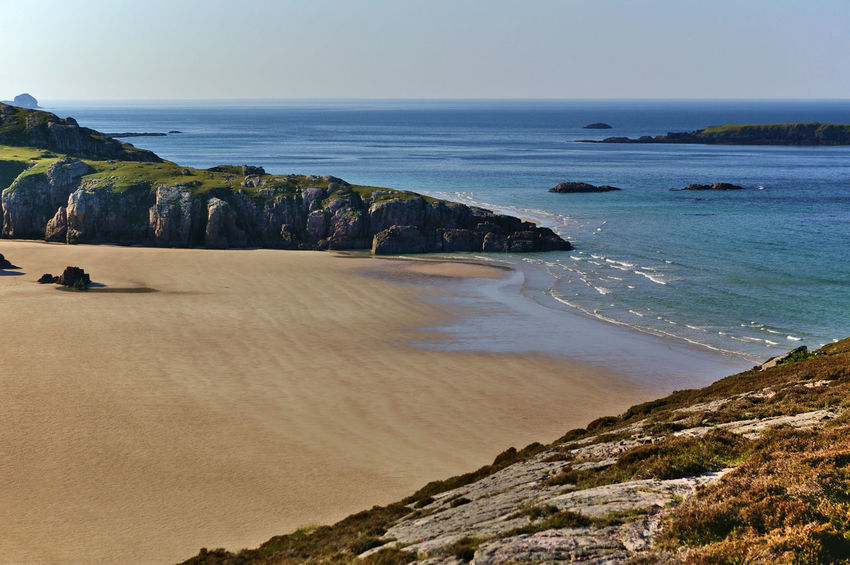 Sandy beach between steep cliffs in the evening sun Scotland Sutherland Beach Beauty In Nature Clear Sky Cliff Day Durness Highlands Horizon Over Water Landscape Nature No People Ocean Outdoors Rock - Object Rock Formation Sand Scenics Sea Sky Tranquil Scene Tranquility Water Wave