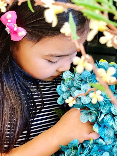 Close-Up Of Girl Smelling Blue Flowers Blooming Outdoors