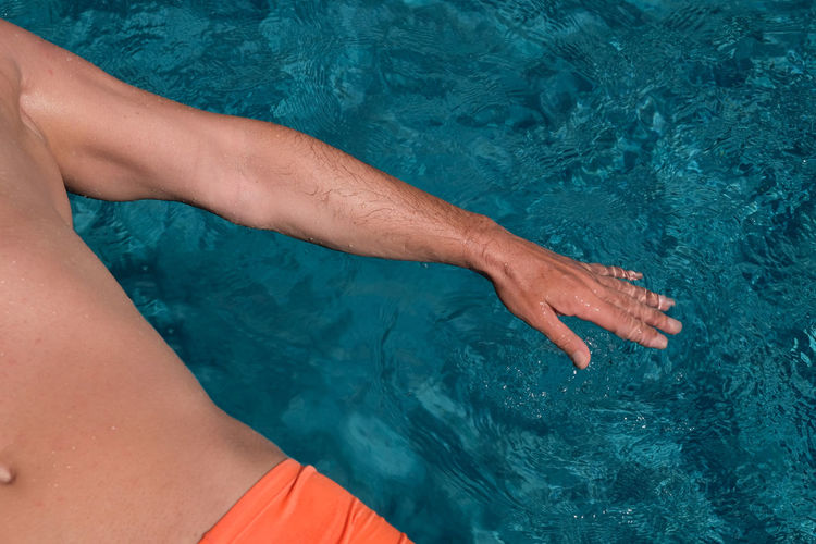 Midsection of man in swimming pool