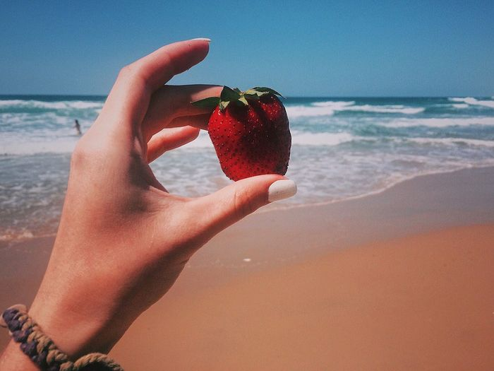 Woman holding strawberry at beach against sky