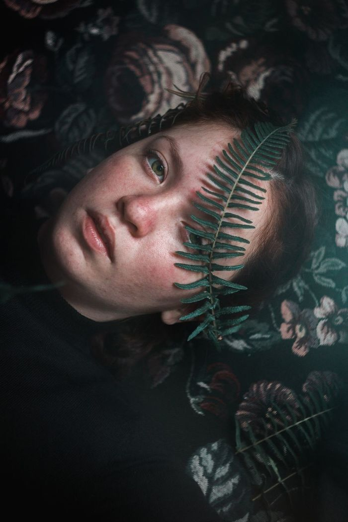 Close-up high angle portrait of young woman lying on pillow with plant