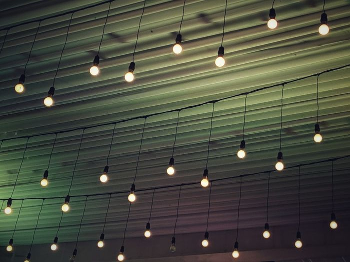 Low angle view of illuminated lights hanging on ceiling