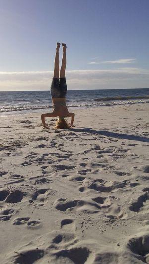 Full Length Of Woman Doing Headstand On Beach Against Sky