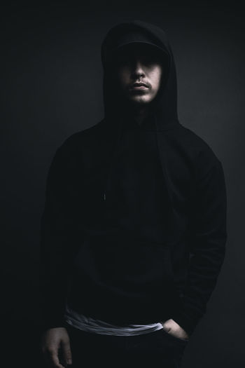 young cool rapper with black hoodie and cap standing in front of grey background Studio Shot Hoodie Hood Black Youth Hip-Hop Rapper Serious Cool Standing Cap Clothing Lifestyle Dark Portrait Shadow Light Front View Hood - Clothing Young Men