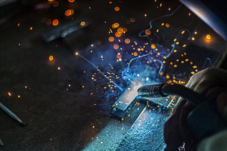 Welding machine generating sparks while heating at workshop