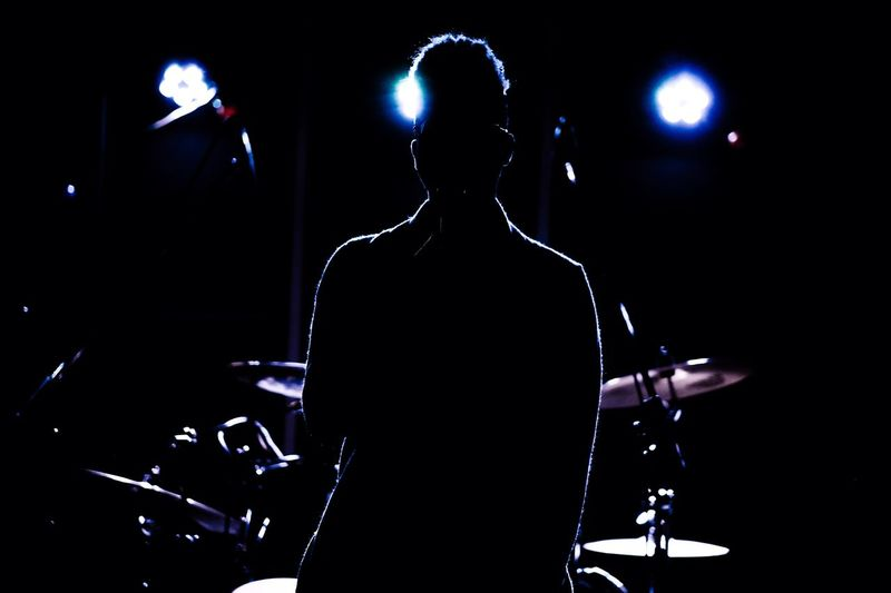 Sillouette of the artist Arts Culture And Entertainment Music Stage - Performance Space Stage Performance Rear View Performing Arts Event Men People Event Light Musician Indoors  Lighting Equipment Illuminated Night Spotlight Stage Light Black Background