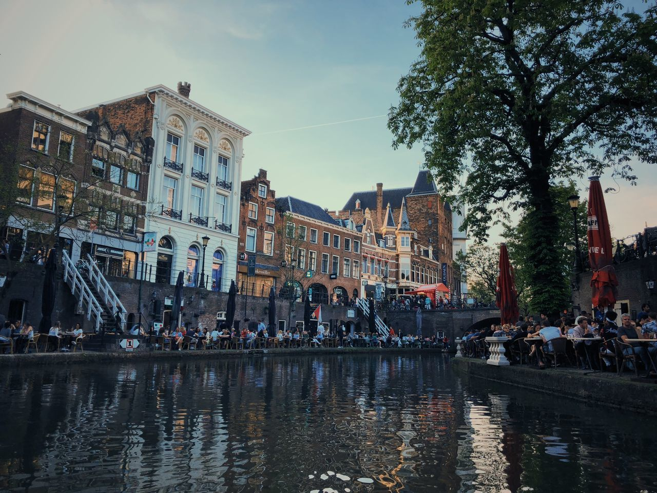 GROUP OF PEOPLE ON BUILDINGS BY CANAL