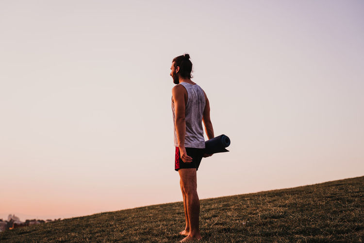 Man standing on field against clear sky
