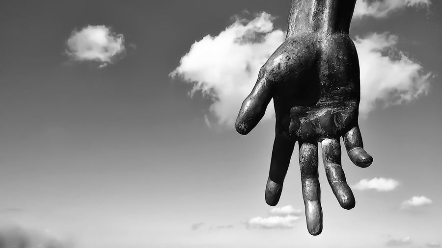 Hand sculpture against sky