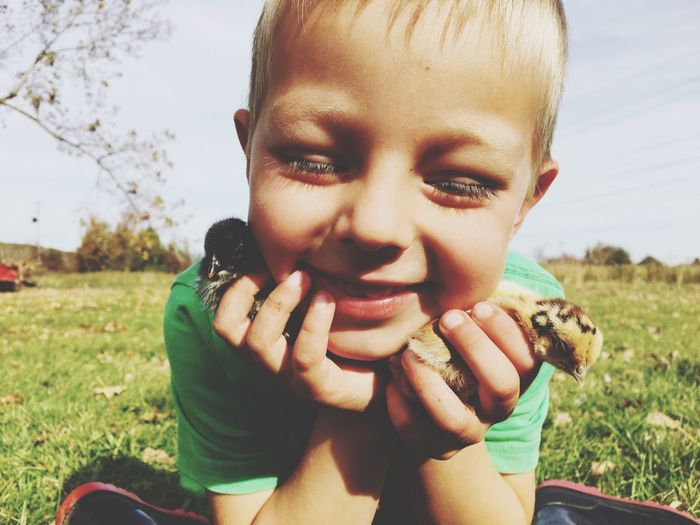 Close-Up Of Smiling Boy With Baby Chickens On Field