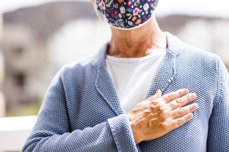 Midsection of senior woman wearing wearing mask gesturing while standing outdoors