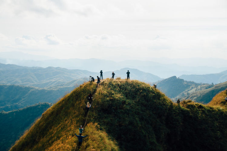 People on mountain against sky