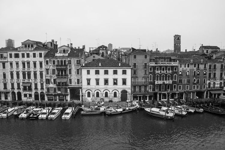 Boats moored in grand canal by buildings against clear sky