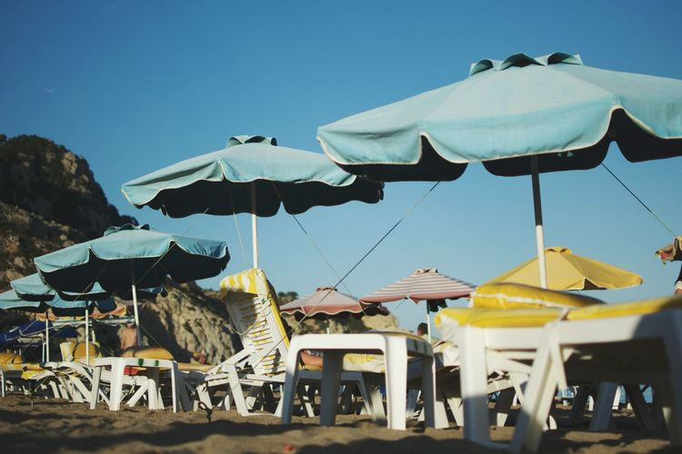 Low angle view of chairs on beach against clear blue sky