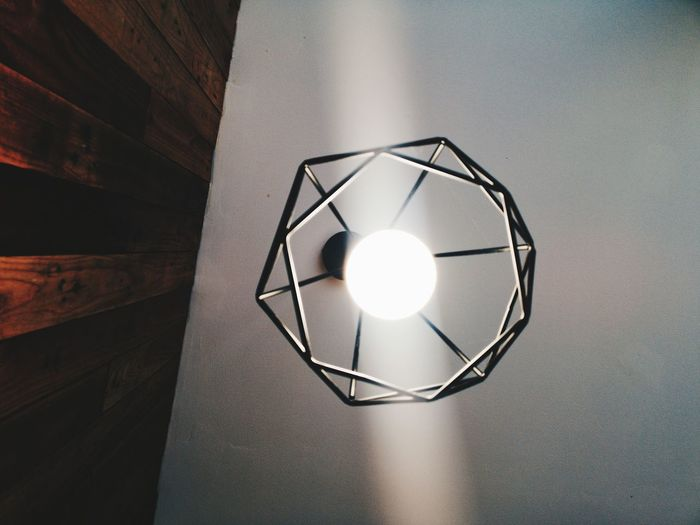 Low angle view of light bulb hanging on ceiling