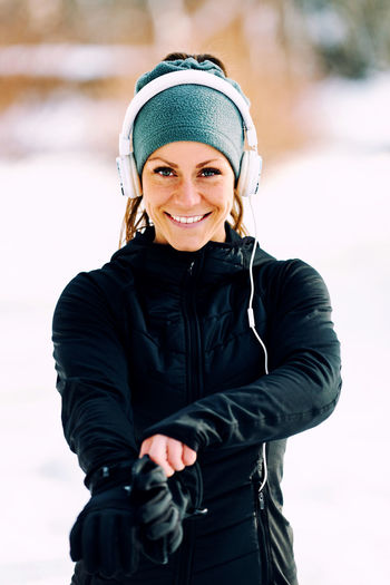 Portrait Of Smiling Woman Listening Music During Winter