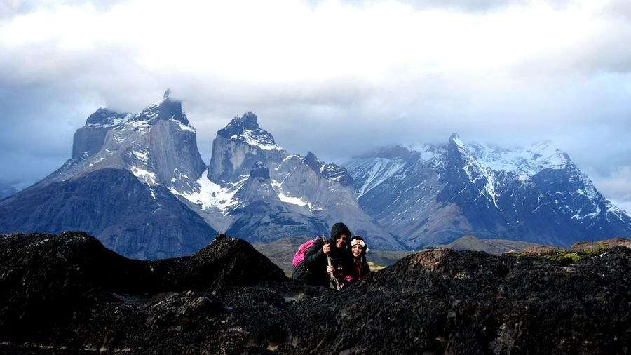 Woman and girl on mountain against snowcapped mountains and sky