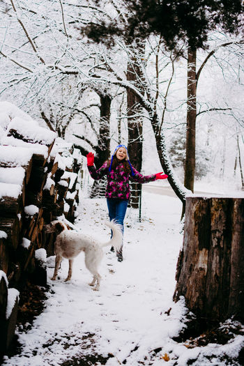 Snow Tree Winter Mammal Animal Themes One Person Domestic Animals One Animal Cold Temperature Full Length Domestic Real People Young Adult Pets Animal Canine Dog Plant Leisure Activity Warm Clothing Pet Owner Outdoors