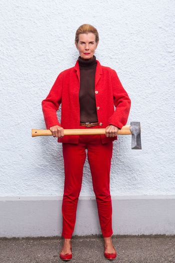 Portrait Of Woman Holding Axe Standing Against White Wall