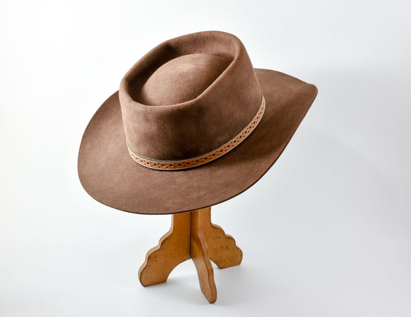 Felt cowboy hat on hat stand. Vintage style hat on stand shot on white background. Country Cowboy Fashion Movie Costume Old West  Rodeo Stetson  Texas Western America American Culture Brown Color Cowboy Hat Felt Hat Hat Hat Stand Headgear Old Style Old Western Style Outdoor Life Ranch House Sherrif Studio Shot Traditional Vintage White Background
