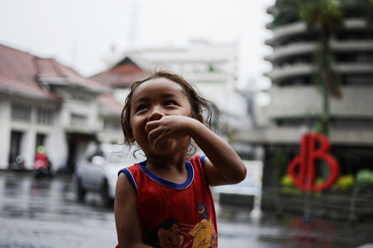 Close-up of smiling girl with finger in mouth against buildings